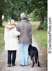 Senior people having a walk with dog