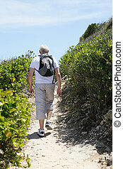 Senior man hiking by the coast