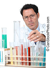 50 years old scientist in a lab behind test tubes