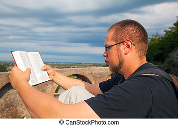 Young man reading the Bible sitting outdoors