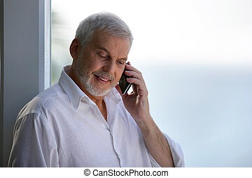 Older man with a phone by a window