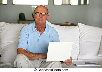 Bald man using laptop at home