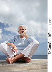 Grey haired man sat on jetty