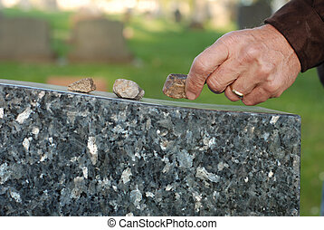 Placing stone on tombstone - Man's hand placing a stone on...