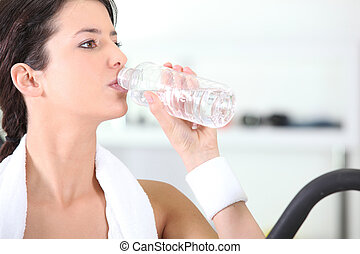 Woman drinking a bottle of water at the gym