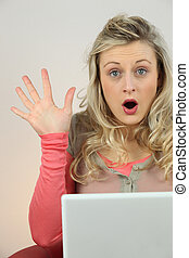 blonde woman surprised behind a computer