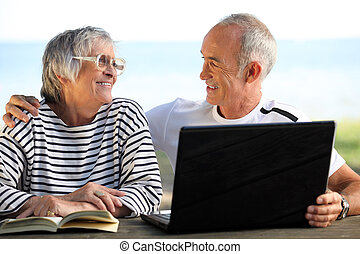 Senior couple in the garden with laptop and book