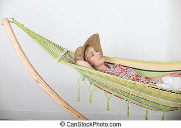 Woman lying relaxing in hammock