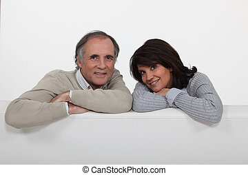 Couple leaning over the backrest of their couch