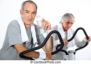 65 years old woman and man doing cardio training