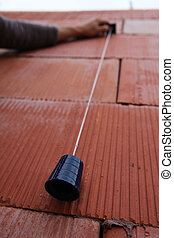Bricklayer using a plumb line