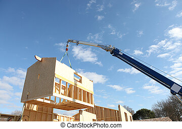 Crane lifting the framework of a house