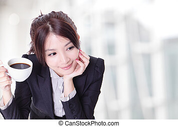 relaxed business woman holding a cup of coffee - Portrait of...