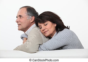 A middle age couple hugging on their couch.