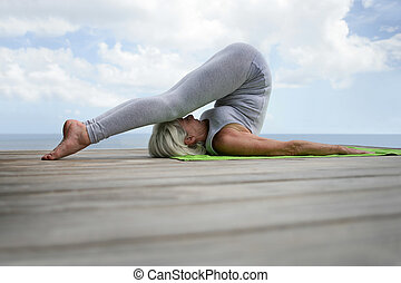 Senior woman doing yoga in a jetty