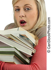 Young woman overworked with a stack of books