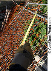 Worker measuring old rusty wire mesh