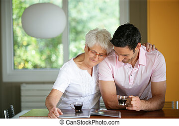 Senior woman drinking coffee with her son