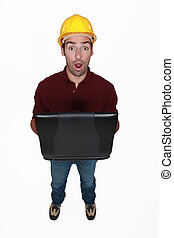 Shocked builder holding laptop