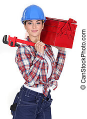 A female manual worker with a toolbox and a wrench.