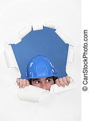 Tradesman peeking out through an opening in a wall