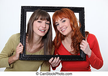 Women poking heads through empty picture frame