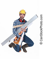 A glowering tradesman carrying building supplies