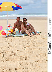 Family sat on the beach by parasol