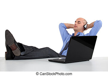 Businessman listening to music on his computer