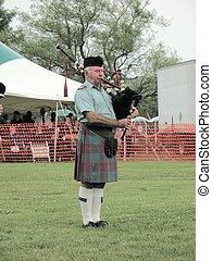 A Scottish Piper Piping - A piper blowing his pipes with his...