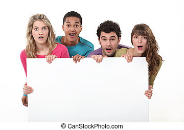 Young people standing behind a blank sign