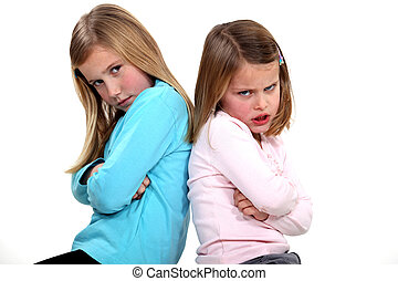 little girls with sulky expression sitting back-to-back