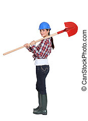 Female manual worker carrying shovel