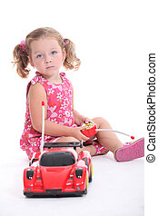 Young girl playing with a remote-control car