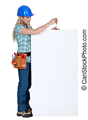 craftswoman fixing an ad board
