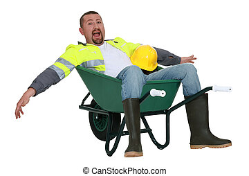 Goofy tradesman sitting in a wheelbarrow