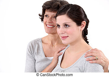 Grandmother holding granddaughter around the shoulders