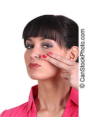 Brunette holding two finger to face