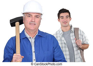 Grey-haired builder with young apprentice
