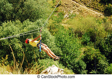 zip line - man descending on a zip-line flying fox