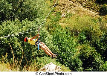 zip line - man descending on a zip-line (flying fox)