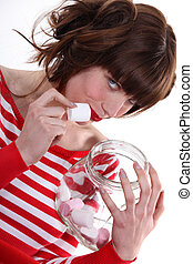 Woman eating marshmallows from a jar