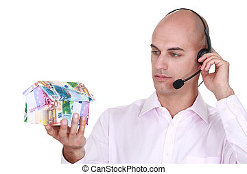 Call center agent holding a house made out of money