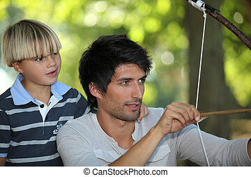 Father teaching his son how to shoot a bow and arrow