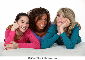 Portrait of three girls resting on white sofa