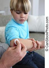 Little boy has grazed his elbow