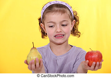 Little girl choosing between apple and pear