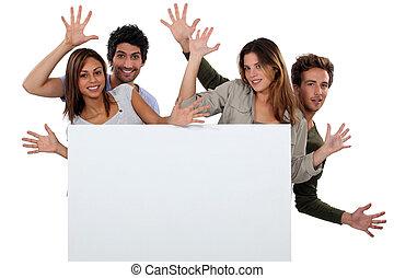 Kids making faces behind white panel