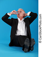 Senior business sat on the floor with champagne flute