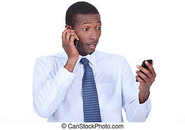 Shocked businessman holding two telephones